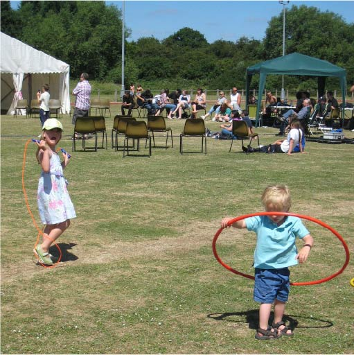 Outdoor children playing with hula hoops in a field